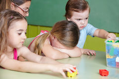 sad-child-crying-kindergarten-children-playing-basketball-getting-comfort-nursery-teacher-38917699