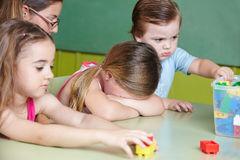 sad-child-crying-kindergarten-children-playing-basketball-getting-comfort-nursery-teacher-38917699